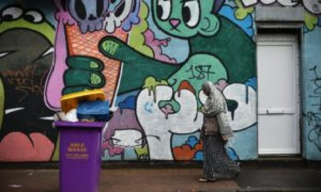 People walk past street art in Stokes Croft, Bristol. Photograph: Rufus Cox/Getty Images