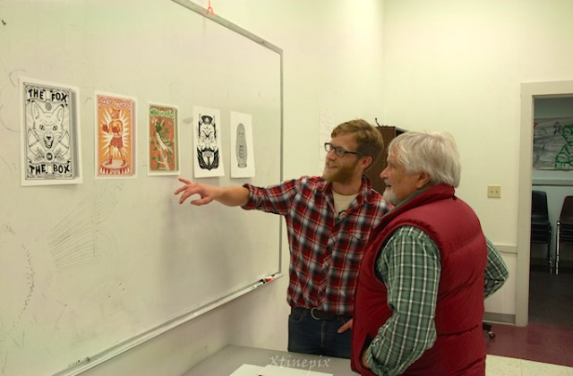 Island Institute Executive Director Peter Bradley gives local artist Norman Campbell the backstory to a piece of art by visiting Sitka Fellow Bene Rohlmann. Photo by