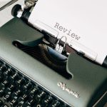 Typewriter with the text 'Review' showing on the paper