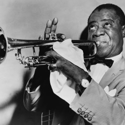 Louis Armstrong playing trumpet, with focused expression