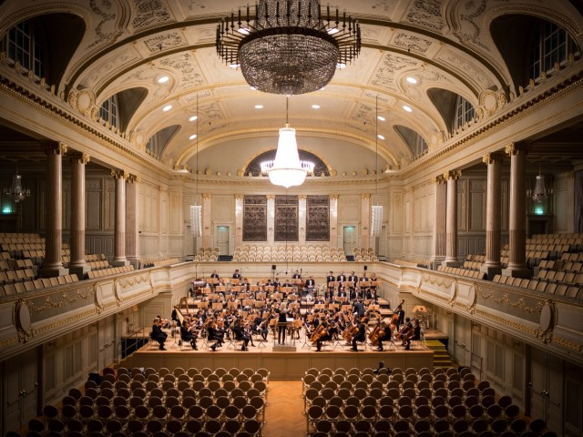Orchestra performing in big hall with empty seats