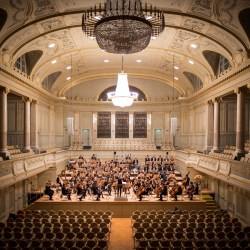 Orchestra playing in big hall with empty seats