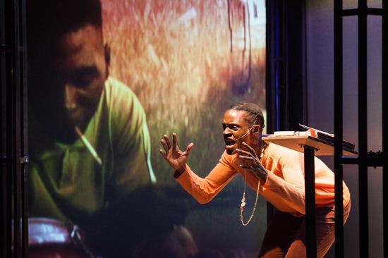 """Okui Okpokwasili yelling, """"Crash!"""" On film at left, a drummer. Photo: Yi-Chun Wu"""