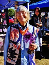 Image contains an older lady wearing a colorful jacket, flowers on her hand. Behind her is an artisan market.