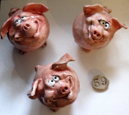 Pictured are three pig sculptures with silly faces. The photo is taken from above and shows the pigs in a triangle formation: two on the top, one a the bottom. A small circle with the number 59 is also situated beside that one pig on the bottom of the photo.