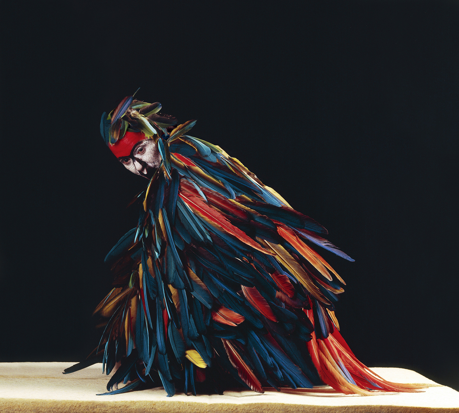 woman covered with feathers in performance pose