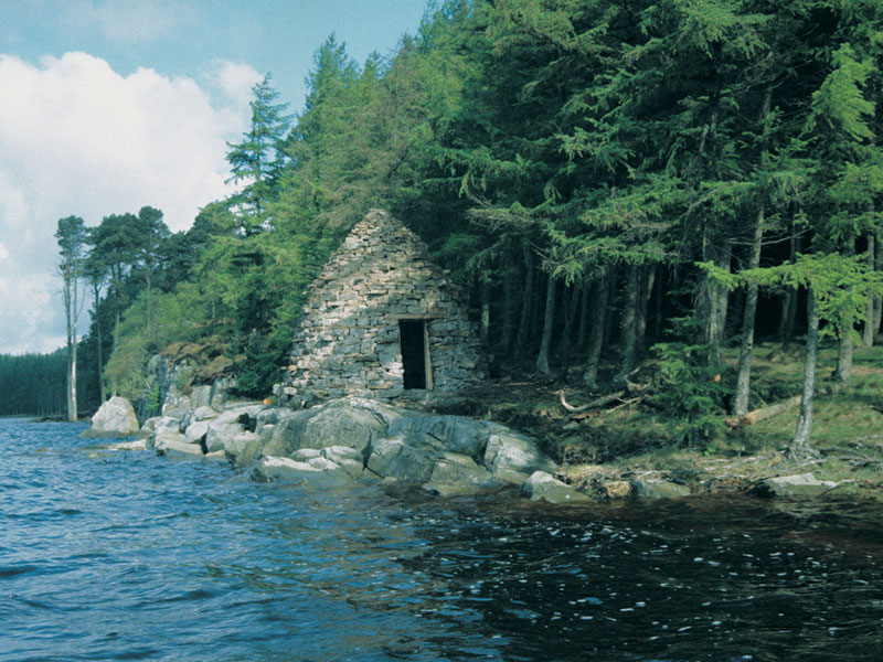 stone hut at edge of water
