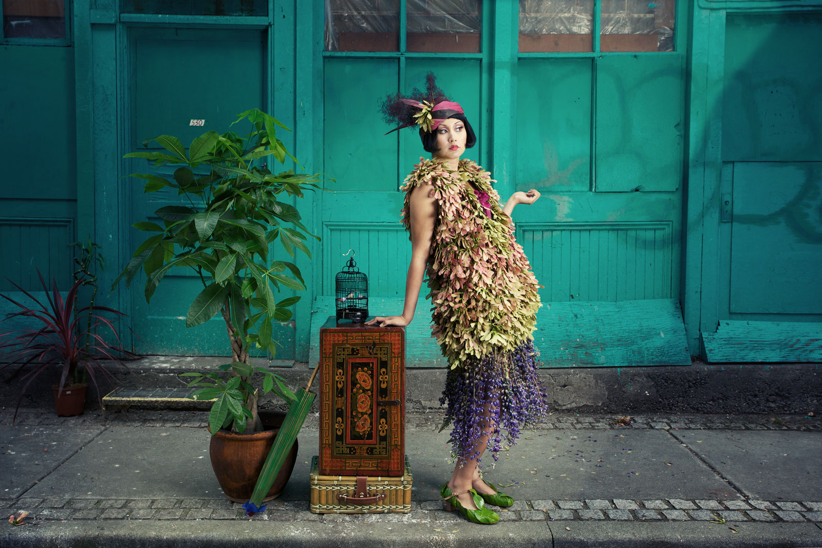 woman in flapper dress made from leaves and other plant materials