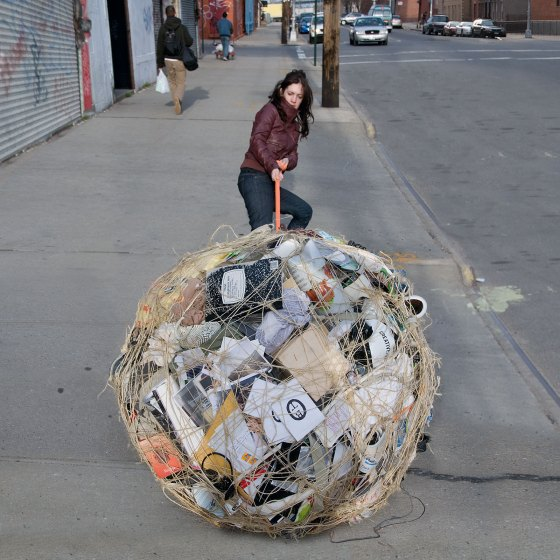 woman pulling bundle of possessions tied with twine