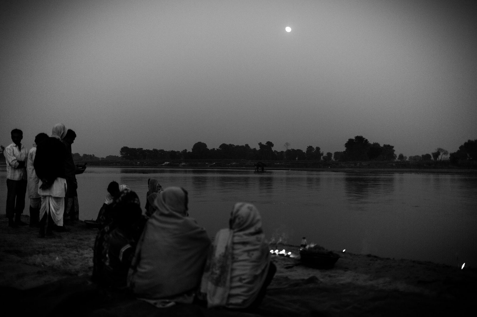 women in Nepal seated by waterfront