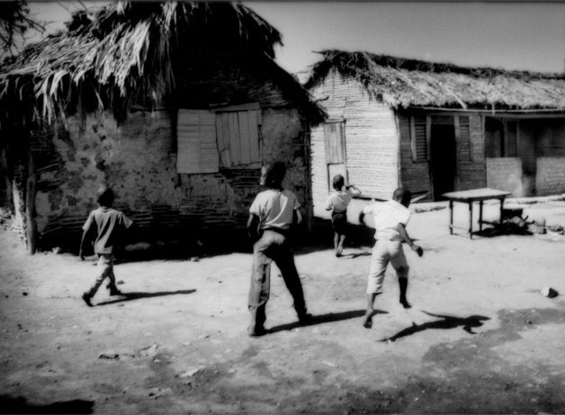 Children born of Haitian descent play among disheveled waddle and daub houses in Batey 2, a group housing area. These children are often denied citizenship within the country, which creates difficulties in obtaining access to health care and continued education. Barahona, Dominican Republic / 2009