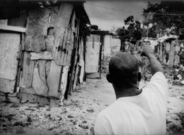A resident of a squalid batey inhabited by Haitian construction workers points directions into the center. The men from this batey work in the construction of new beachfront hotels and condominiums while their families live without access to water, healthcare, or education. Boca Chica, Dominican Republic / 2009