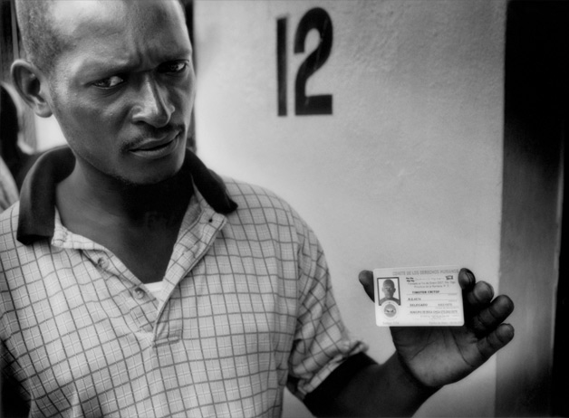 Timoter, a Haitian national who like many others has worked for years in the Dominican Republic without citizenship, holds a counterfeit registration card sold to him by a con man. Workers are frequently deported prior to receiving final payments and children are often denied access to education based on citizenship. Boca Chica, Dominican Republic / 2009