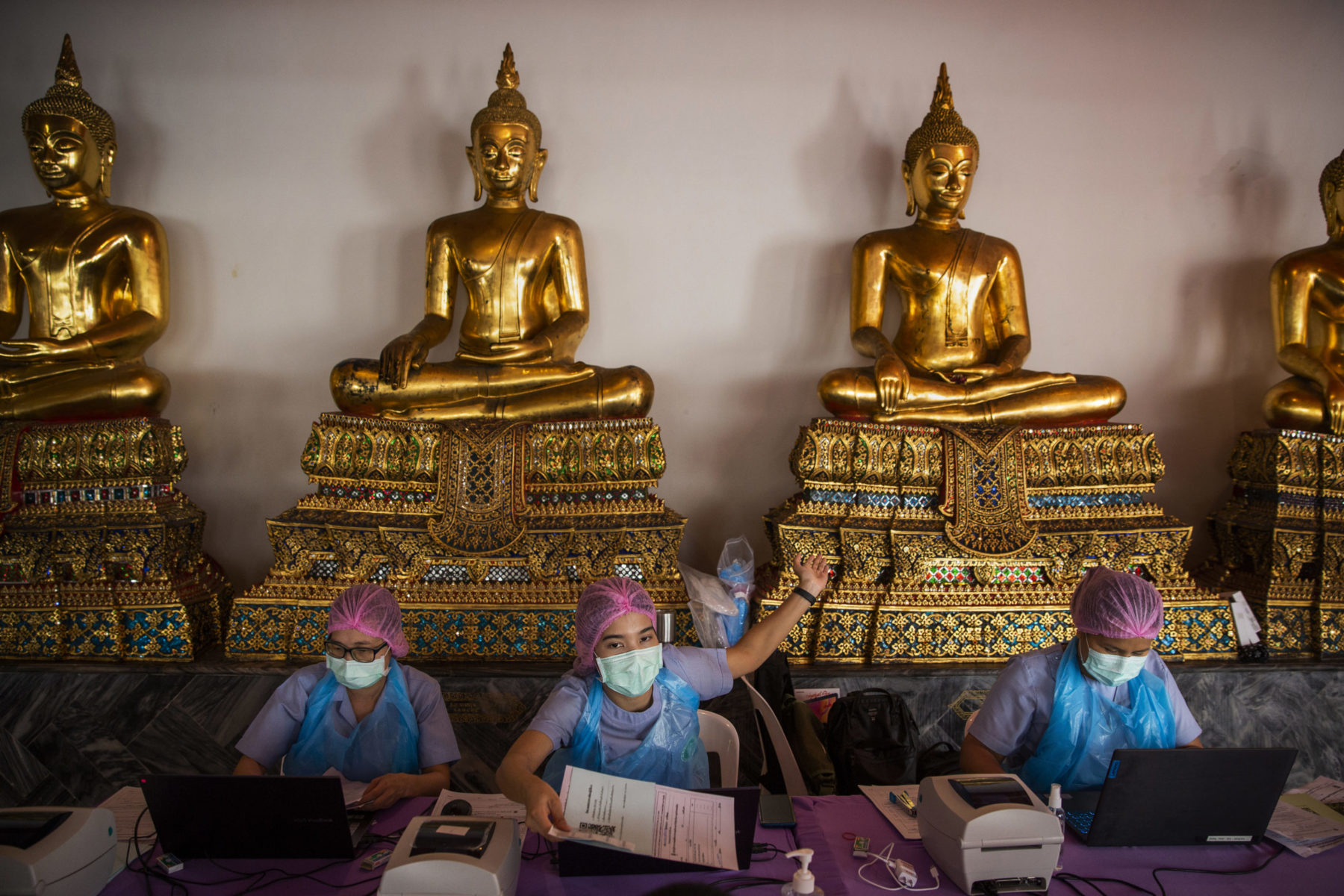 Three healthcare workers with gloves and masks sit in front of statues at a monestary.