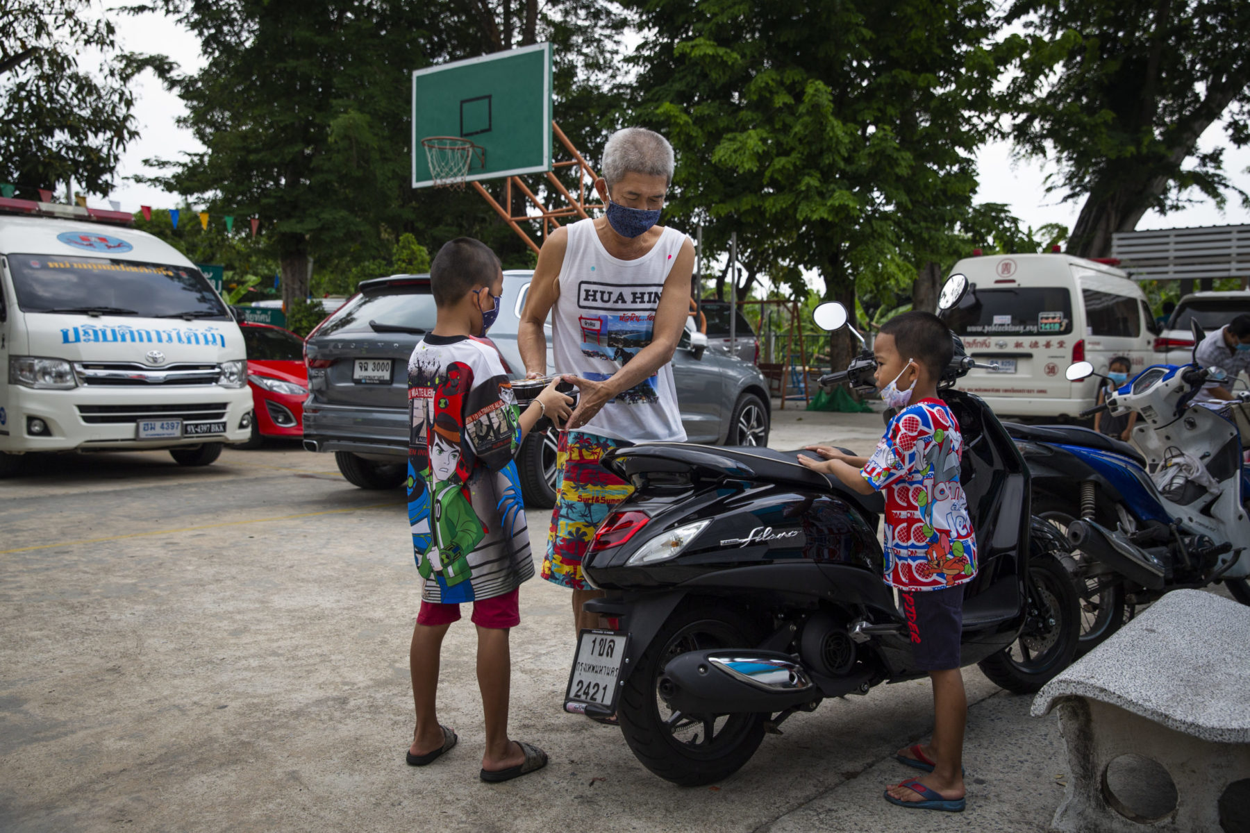 A grandfather hands meals to two grandchildren next to their motorcycle.