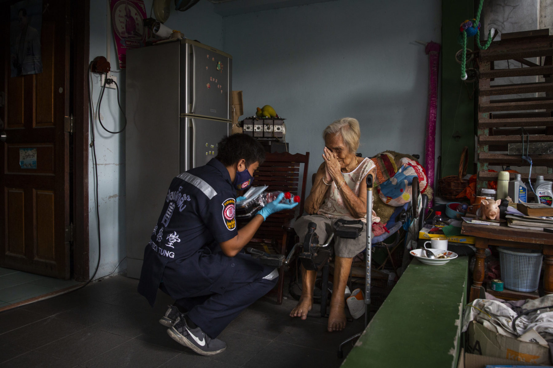 A masked healthcare worker assists an elderly person in their home.