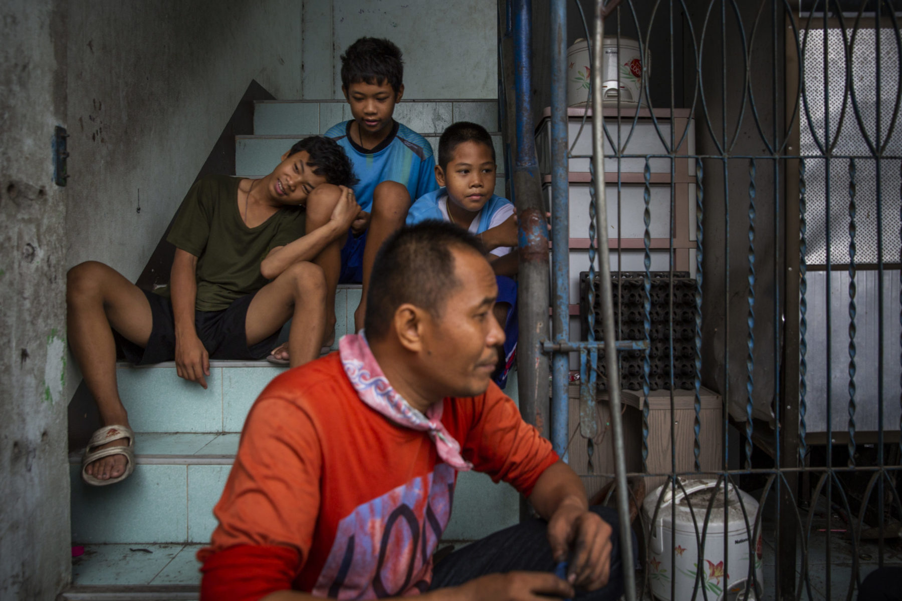 A man sits in front of his three children who are sitting on a staircase.