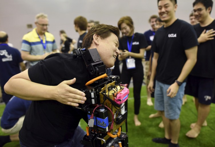 A man from a U.S. team hugs a humanoid robot after they won against an Iranian team during the 2015 Robocup finals in Hefei