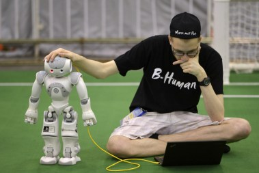 A member from a German team adjusts a humanoid robot during the 2015 Robocup finals in Hefei