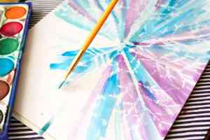 Watercolour and Oil Pastel Resist Snowflake Kids Art - This watercolour and oil pastel resist Snowflake art idea for kids is perfect for the Winter season. Children will love discovering the secret snowflake, while playing with and mixing the watercolour paints to create a pretty Winter scene.