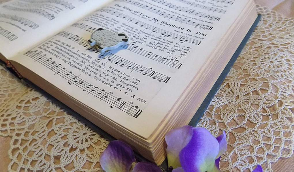 Picture of Hymnal with a little sheep laying on it and purple flowers tucked in the corner