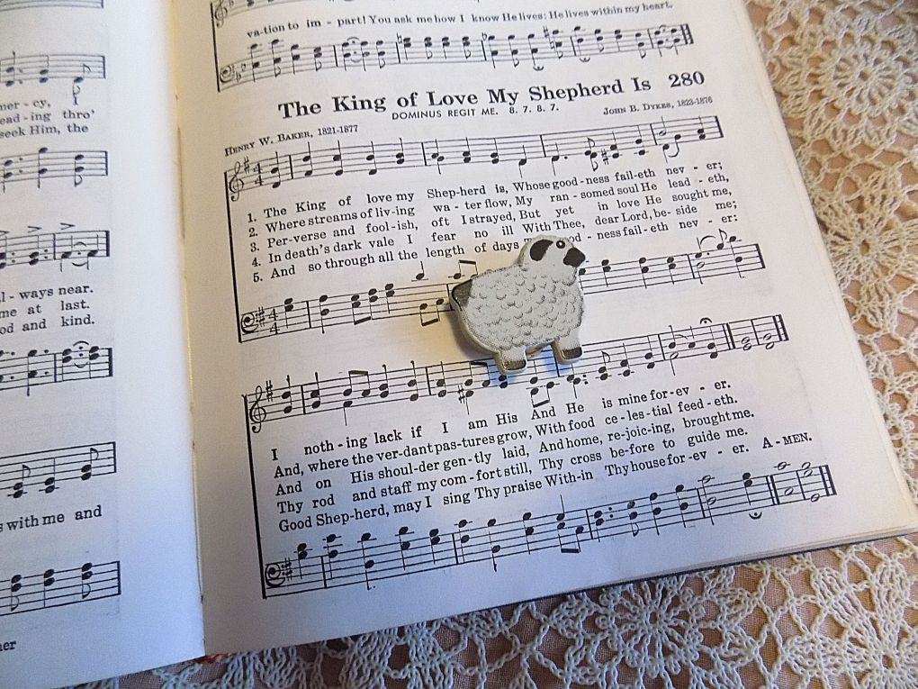 Sheep lying on hymn book open to The King of Love My Shepherd Is