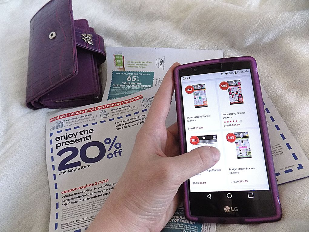 Picture of hand shopping on a phone, coupons, and a purple wallet to illustrate contentment and Proverbs 31:11