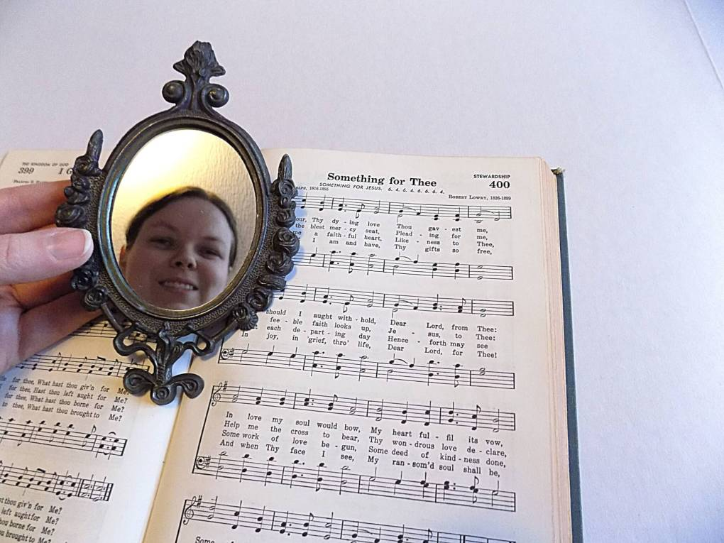 Picture of a face reflected in a mirror held over a hymnbook