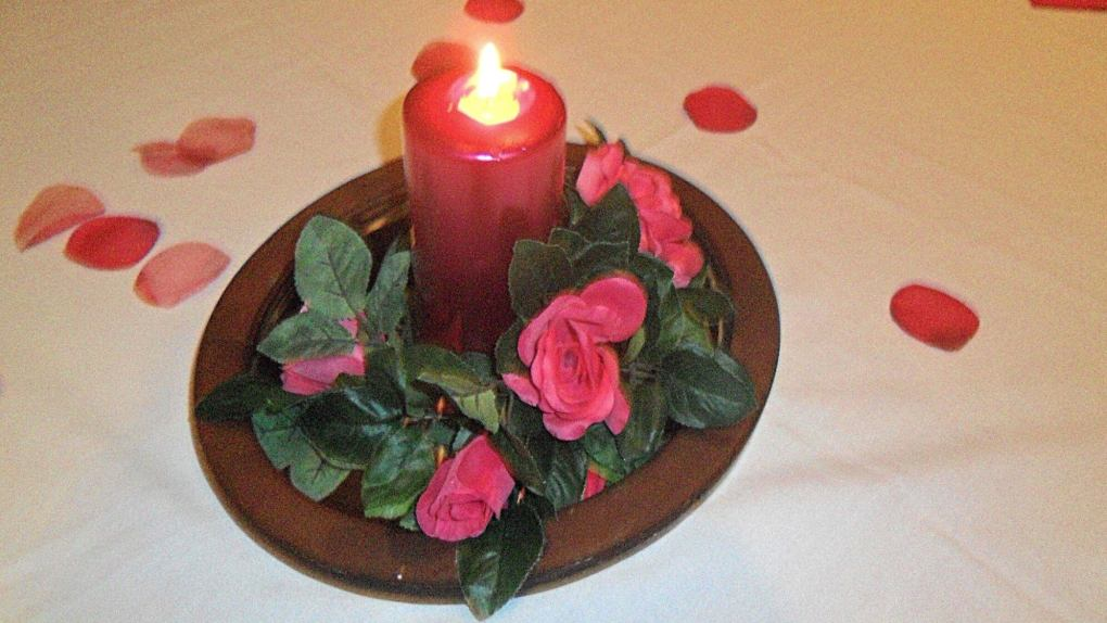 Picture of a pink candle burning and pink roses and rose petals