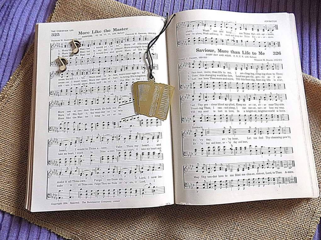 Hymnal with gold accordion bookmark and tiny wooden music notes