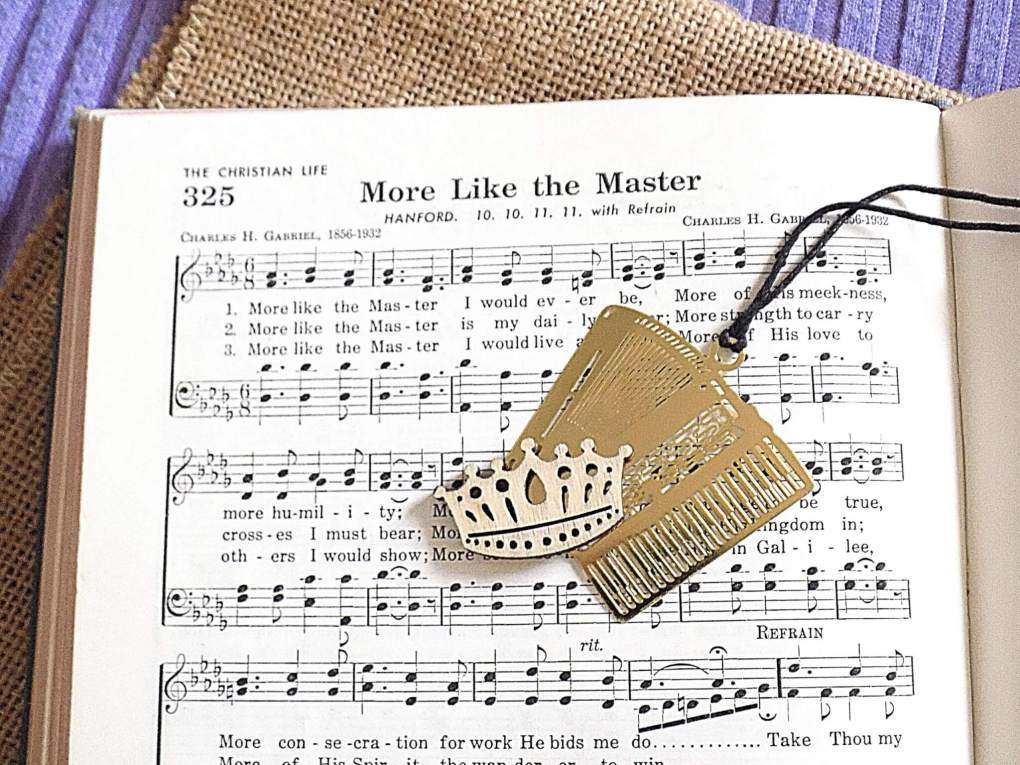Hymnal with gold accordion bookmark and little wooden crown