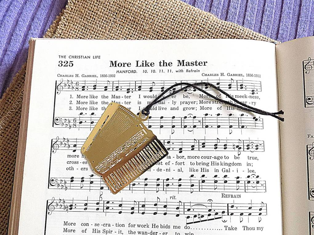 Picture of hymnal and gold accordion bookmark on burlap and lavender background