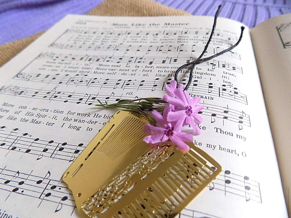 Gold accordion bookmark and purple flowers on hymnal