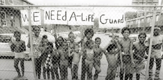 Children line up behind a fence and there is a sign that says we need a life guard.