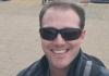 white man smiling with dark sunglasses.