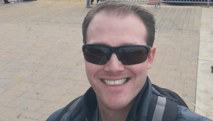 white man smiling with dark sunglasses.