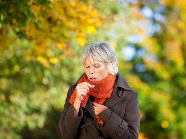 21246808 – senior woman in jacket suffering from cough in park