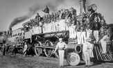 Members of the 1925 Million Dollar Band standing on and in front of a steam train.