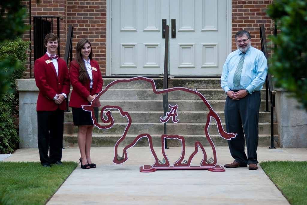 Dean Olin and two students with elephant-shaped Plexiglas bank