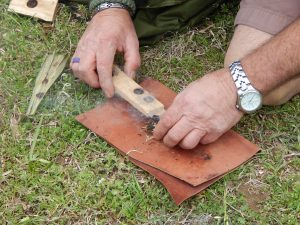 A flint knapper demonstrates how to break down flint into tools and weapons.