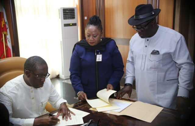 Delta State Governor, Senator Ifeanyi Okowa (left), assisted by the Speaker of the State House of Assembly, Rt Hon Sheriff Oborevwori (right), and the Clark of the House, Mrs Lyna Ocholor, signing into Law, the Delta State Public and Private Properties Bill, 2018 and the Delta State Oil Producing Areas Development Commission (Amendment) Bill, 2018.