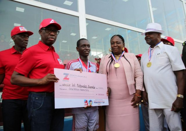 Delta State Governor, Senator Ifeanyi Okowa (2nd left); Commissioner for Basic and Secondary Education, Mr. Chiedu Ebie (left); Chief and Mrs. Charles Obule (right); presenting a Cheque of One Million Naira to the Team Captain of Obule Boys Integrated School, Neye Jolomi as the winner of 2018/2019 Edition of Zenith Bank Delta State Principals Cup Finals.