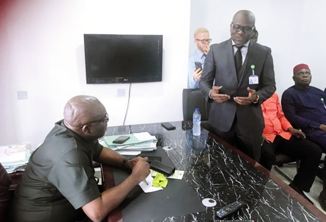 Delta Commissioner for Lands, Chuchill Amagada looks on as the Chairman, Delta Assembly Lands Committee, Reuben Izeze Speaks during the visit