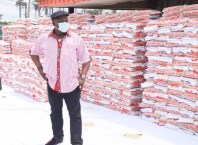 Speaker Oborevwori Standing Behind Bags of Rice He Donated to His Constituents
