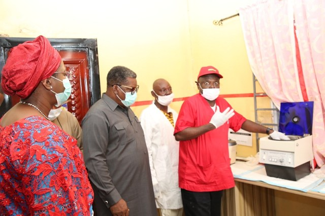The wife of the Delta State Governor and founder O5 Initiative, Dame Edith Okowa (Left), the Commissioner of Health, Dr. Mordi Onoye (Left) listening to Dr. Clement Isibor explaining the functions of the blood screening machine at the Akwukwu-Igbo General Hospital (Pix: Norbert Amede)