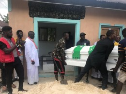 Hon Samuel Mariere (in white attire) watches as pallbearers move the body of his Mum to its final resting place.