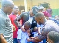 Olorogun Jaro Egbo helping a Pupil with his new Uniform