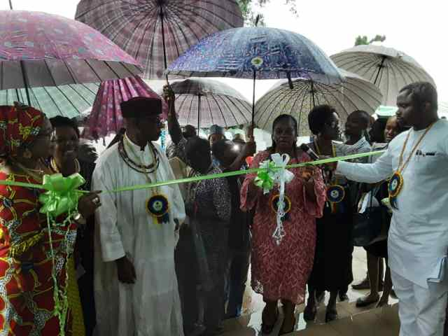 The Director, Support Services, NGC, Mrs. Uche Ossai, cutting the tape at the Commissioning of the Evboesi Health Centre built by NGC, while the enogie of Evboesi, HRH Ogiefo Festus Iduozee JP, others watch.