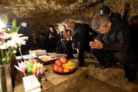 チビチリガマの中で手を合わせる遺族ら=7日午後1時28分、沖縄県読谷村波平、代表撮影