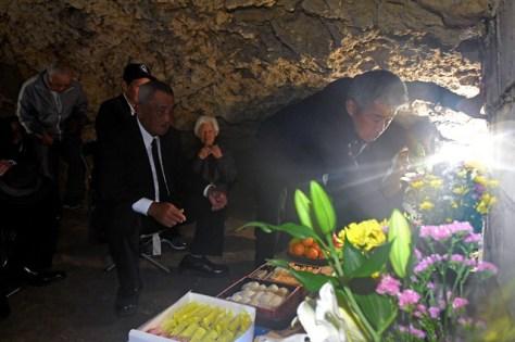 ガマの中に設けられた祭壇に線香をあげ、犠牲者の冥福を祈る遺族ら=7日午後、沖縄県読谷村波平のチビチリガマ、代表撮影